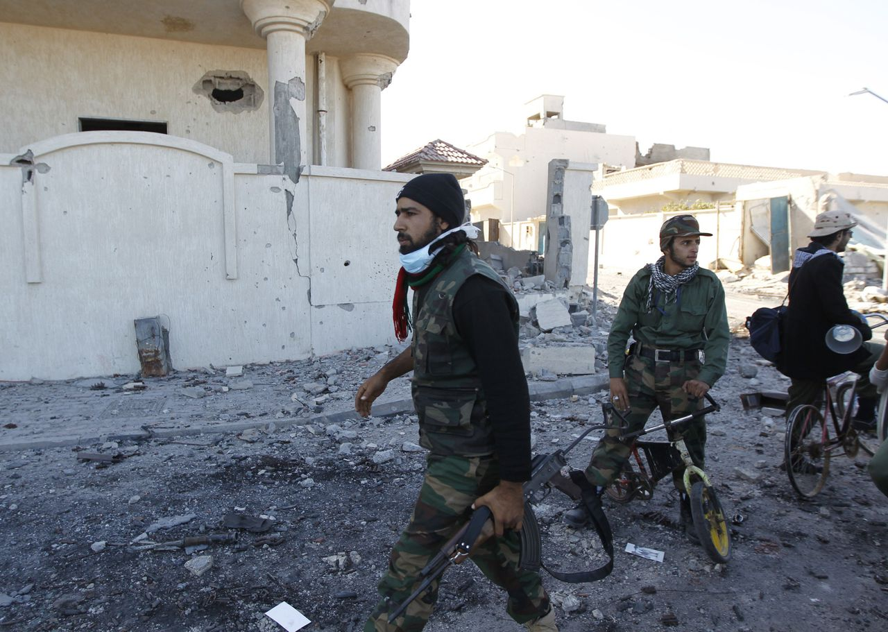 Anti-Gaddafi fighters walk past a damaged building in Sirte October 21, 2011. Former Libyan leader Muammar Gaddafi, on the run for more than two months, was tracked down and killed in his hometown Sirte by opposition fighters on Thursday. REUTERS/Thaier al-Sudani (LIBYA - Tags: CIVIL UNREST POLITICS)