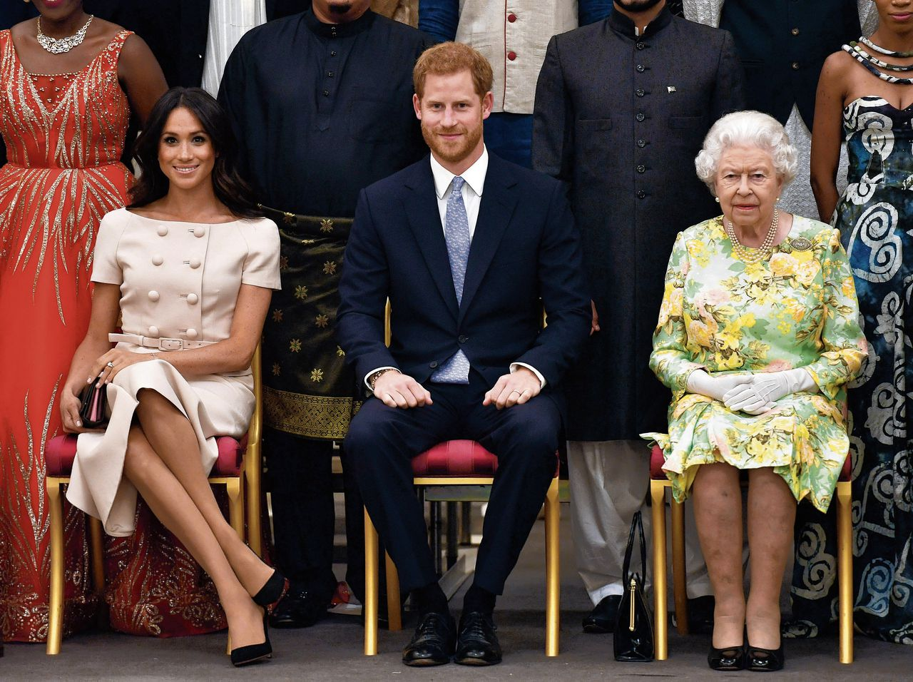 Koningin Elizabeth, prins Harry en Meghan in 2018 in Buckingham Palace.