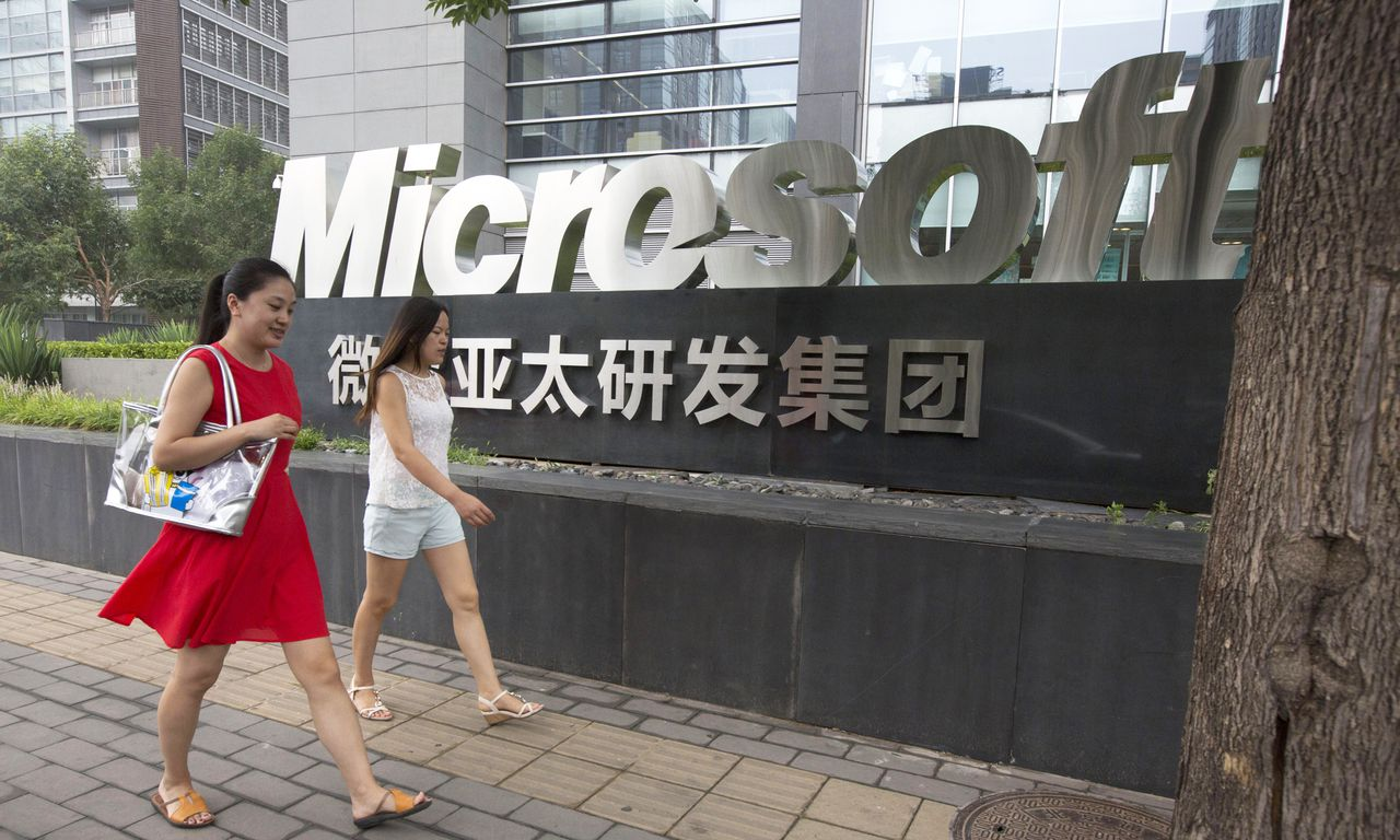 In this photo taken Thursday, July 31, 2014, women walk past the logo for Microsoft in Beijing, China. Chinese regulators have launched a series of anti-monopoly investigations of global automakers and technology providers, stepping up pressure on foreign companies that feel increasingly unwelcome in China. Microsoft is under investigation regarding its Windows operating system and how it handles compatibility, bundling and publication of documentation, according to the State Administration for Industry and Commerce. (AP Photo/Ng Han Guan)
