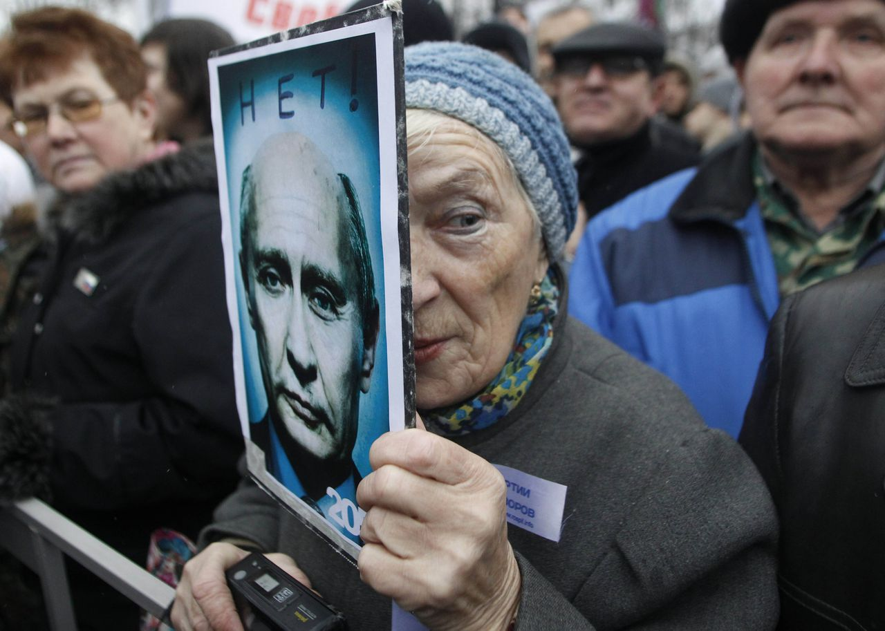 "A demonstrator holds a poster showing a manipulated photograph of Russian Prime Minister Vladimir Putin and bearing the words, ""No! 2050"" during a mass rally to protest against alleged vote rigging in Russia's parliamentary elections in Moscow, Russia, Saturday, Dec. 10, 2011. Tens of thousands of people held the largest anti-government protests that post-Soviet Russia has ever seen on Saturday to criticize electoral fraud and demand an end to Vladimir Putin's rule. (AP Photo/Mikhail Metzel)"