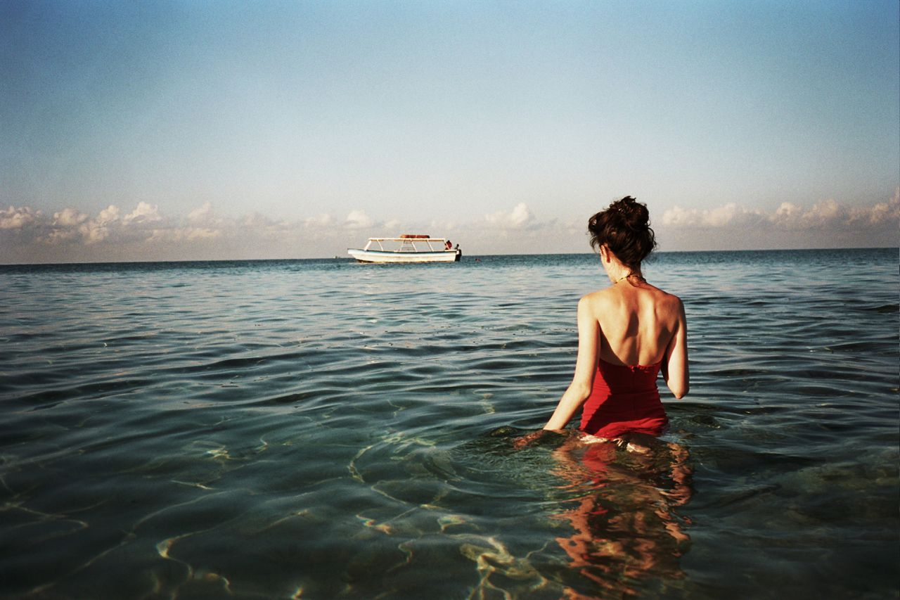 Jamaica --- Woman wading in sea --- Image by © Magdalena Wosinska/Corbis