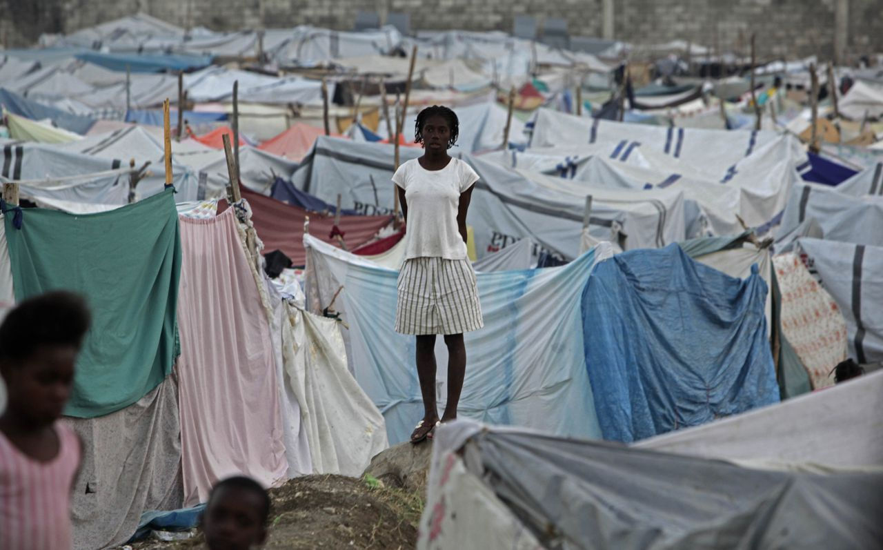 Musicalsterren voor Haïti Foto AP A woman stands in a makeshift tent camp for earthquake survivors in Port-au-Prince, Friday, Feb. 5, 2010. A half-million Haitians who fled their shattered capital after the earthquake are starting to return to a maze of rubble piles, refugee camps and food lines, complicating ambitious plans to build a better Haiti. (AP Photo/Ramon Espinosa)