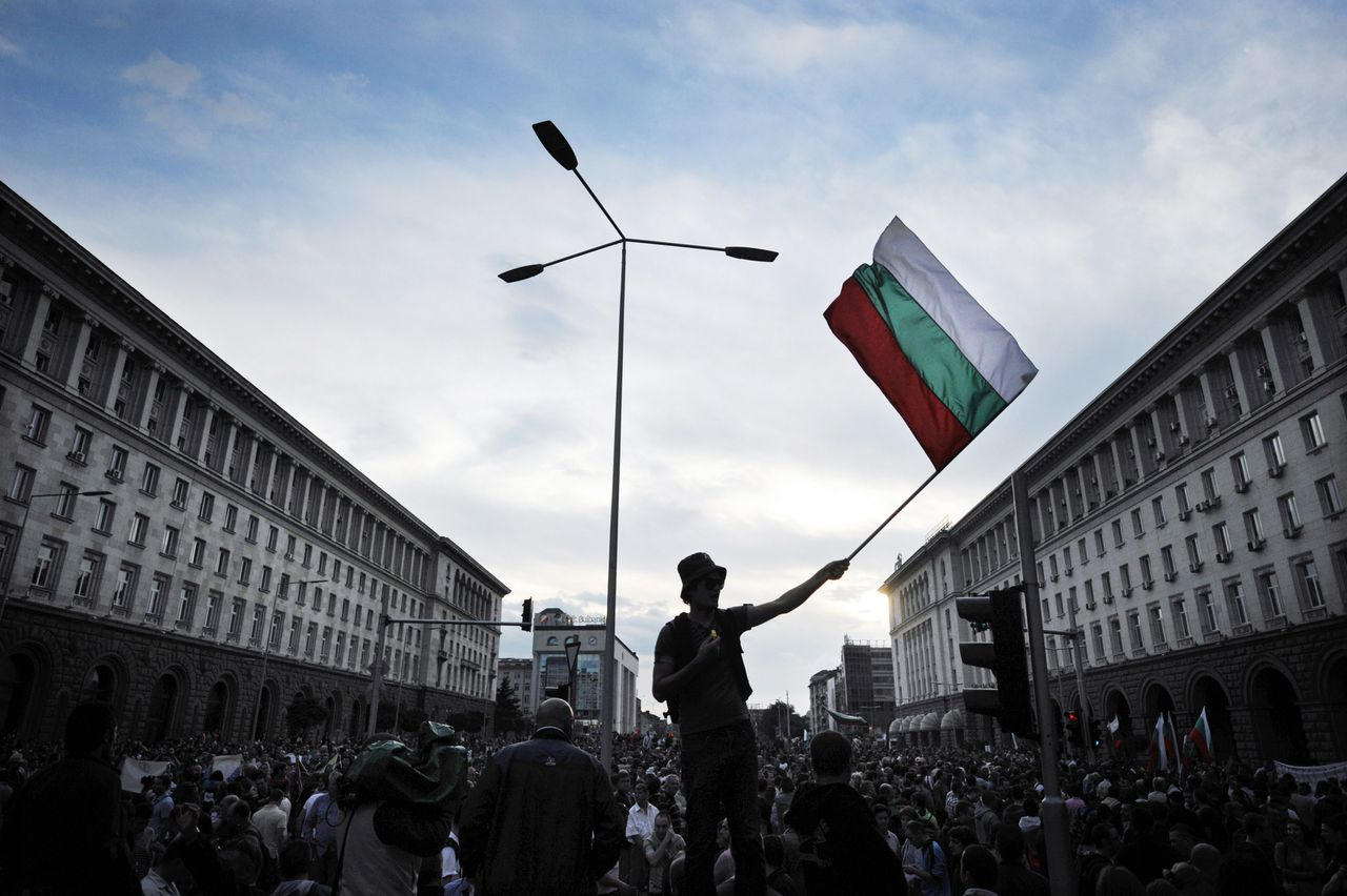 A demonstrator holds a Bulgarian flag during a protest outside the government headquarters in downtown Sofia on June 14, 2013, against the appointement of the new head of the DANS national security agency. The surprise appointment of a controversial young MP and media mogul to head Bulgaria's powerful national security agency DANS on Friday drew fury from the president and brought thousands of protesters to the streets. Delyan Peevski, a 32-year-old deputy from Turkish minority party MRF whose family owns several newspapers, TV channels and websites, was confirmed today as head of the DANS by parliament after being nominated by new Prime Minister Plamen Oresharski. TOPSHOTS/AFP PHOTO / DIMITAR DILKOFF