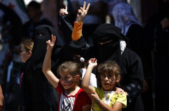 Syriërs maken een vredesgebaar tijdens een demonstratie tegen het regime van Assad, in juni in de Syrische stad Idlib.
