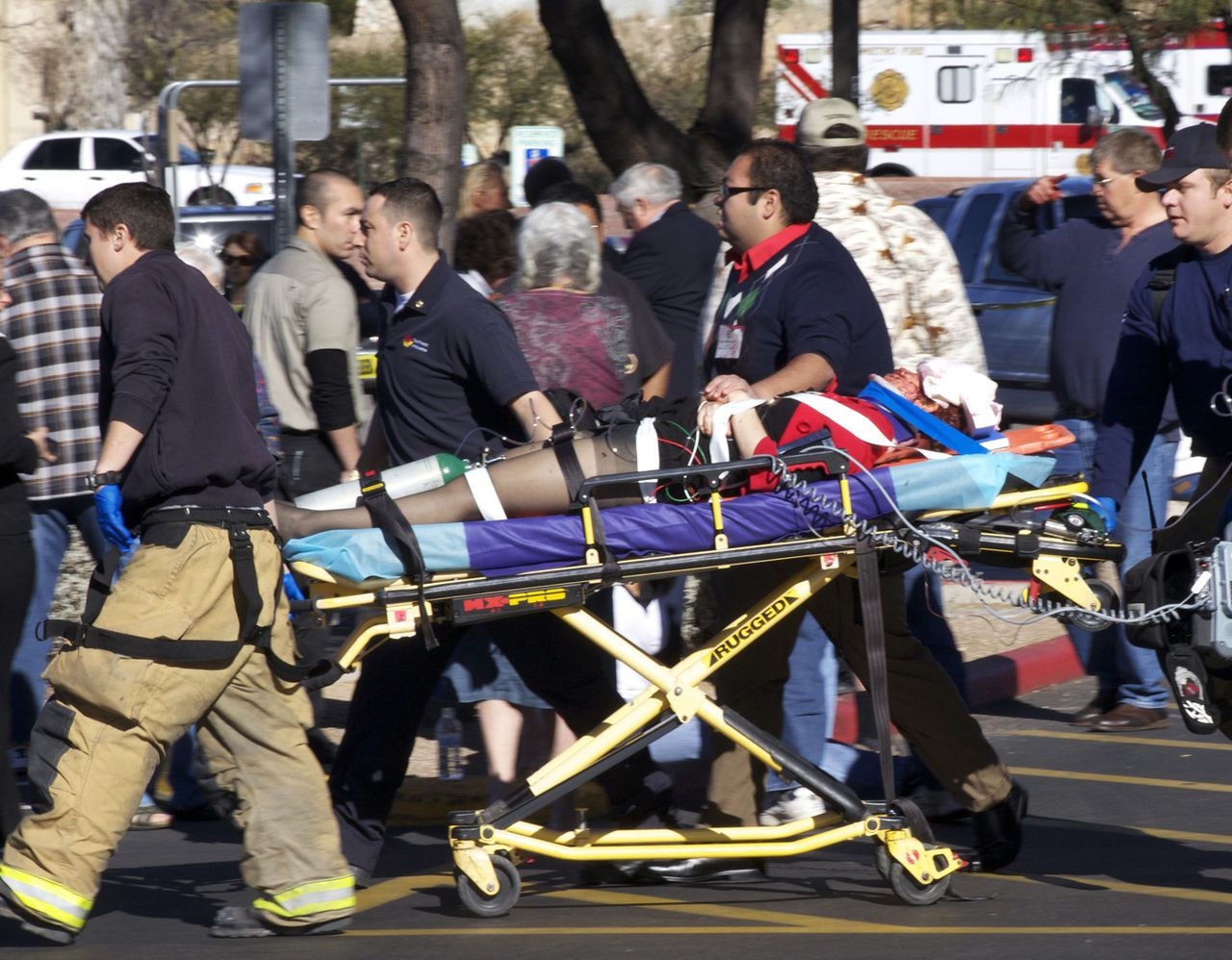 ** ADDS NAME OF VICTIM, REP. GABRIELLE GIFFORDS ** Emergency personnel use a stretcher to move Rep. Gabrielle Goffords, D-Ariz., after she was shot in the head outside a shopping center in Tucson, Ariz. on Saturday, Jan. 8, 2011. (AP Photo/James Palka)