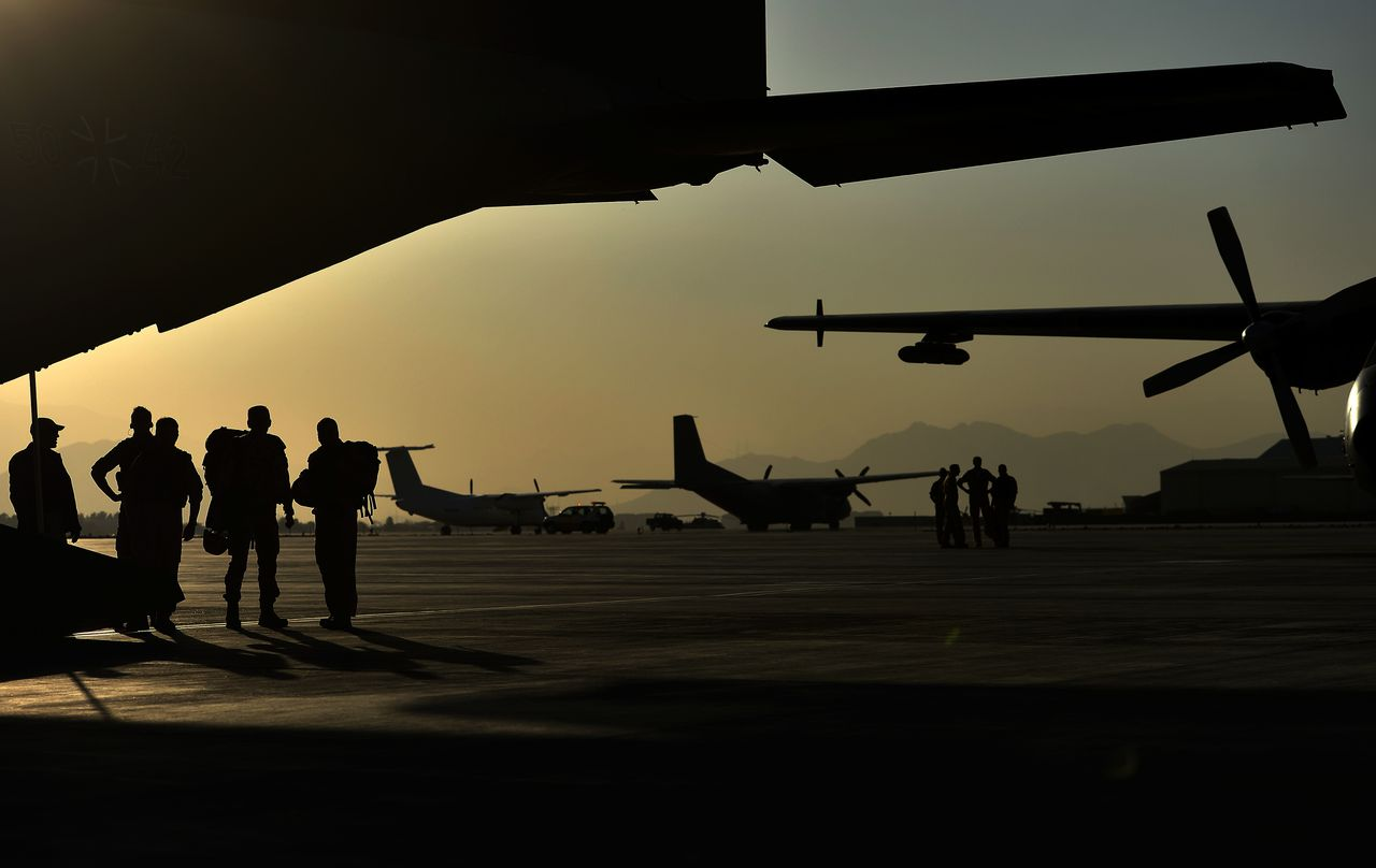 Soldiers of the German Army Bundeswehr stand next to a cargo plane Transall C-160 at the international airport in Kabul, Afghanistan on November 12, 2012. German Defence Minister Thomas de Maiziere said Monday, November 12, 2012 on a visit to Afghanistan that his government would decide in the coming days on the next steps in withdrawing troops from the country. AFP PHOTO / POOL/ OLIVER LANG