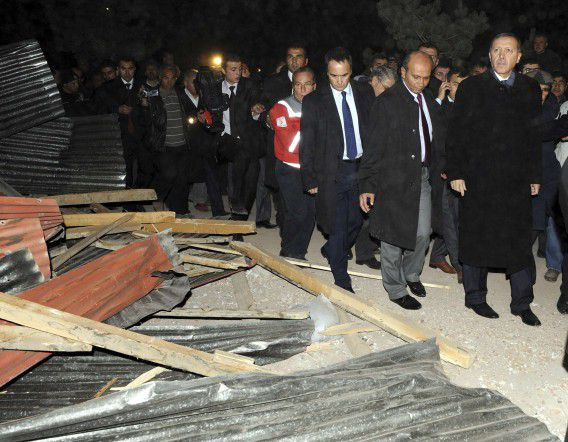 Turkey's Prime Minister Tayyip Erdogan (R) visits Ercis after an earthquake, near the eastern Turkish city of Van, late October 23, 2011. At least 138 people were killed in a powerful earthquake that struck southeast Turkey on Sunday, but the number still buried beneath the rubble in the province of Van is still unknown, Erdogan said. REUTERS/Abdurrahman Antakyali/Anadolu Agency (TURKEY - Tags: DISASTER ENVIRONMENT POLITICS) FOR EDITORIAL USE ONLY. NOT FOR SALE FOR MARKETING OR ADVERTISING CAMPAIGNS. THIS IMAGE HAS BEEN SUPPLIED BY A THIRD PARTY. IT IS DISTRIBUTED, EXACTLY AS RECEIVED BY REUTERS, AS A SERVICE TO CLIENTS. TURKEY OUT. NO COMMERCIAL OR EDITORIAL SALES IN TURKEY