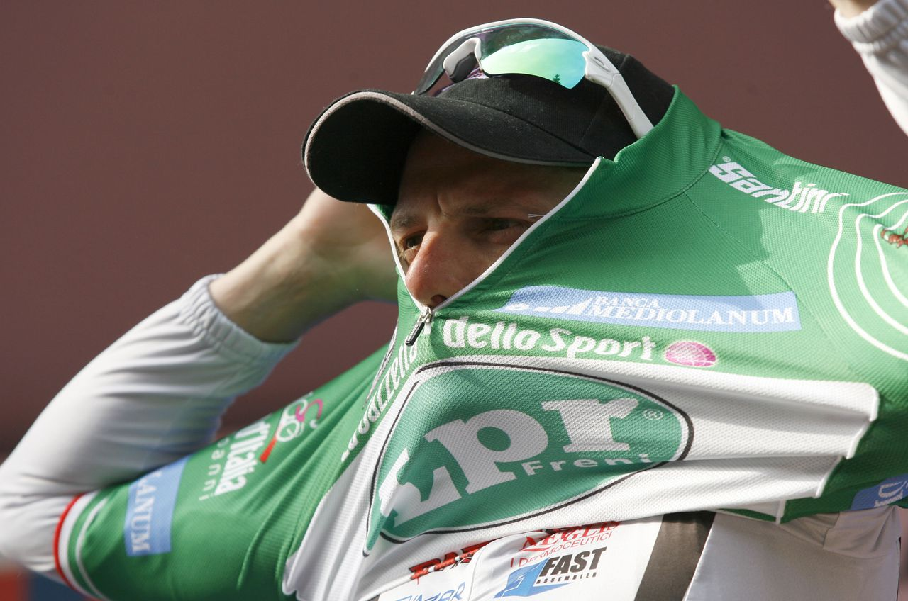 Danilo di Luca trekt de groene trui aan als leider van het klimmersklassement in de Ronde van Italië. Foto APItaly's Danilo Di Luca puts on the green jersey of the best climber as he stand on the podium after winning the fourth stage of the Giro d'Italia, Tour of Italy cycling race, from Padua to San Martino di Castrozza, Tuesday, May 12, 2009. (AP Photo/Marco Trovati)