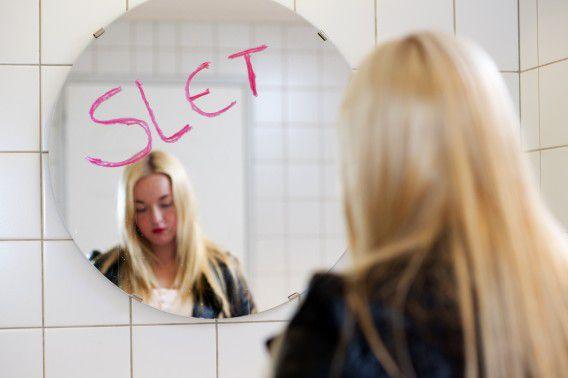 ILLUSTATIE - Een scholiere staat oog in oog met scheldwoorden op de spiegel van een toilet. ANP XTRA ROOS KOOLE
