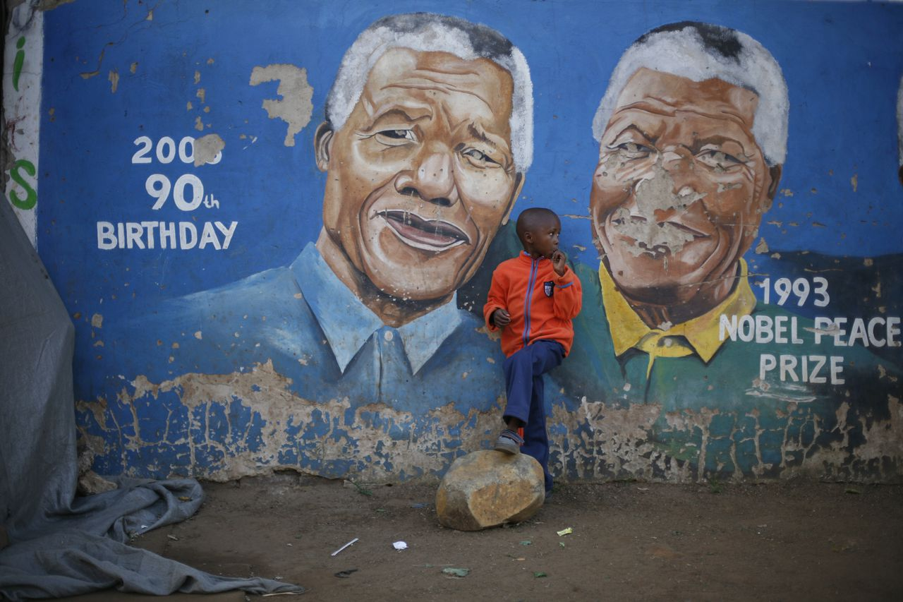 """Hussein Gallo, 7, stands by a mural of Nelson Mandela in the Soweto township in Johannesburg, South Africa, Saturday June 7 2013. Former South African President Nelson Mandela is in """"serious but stable"""" condition after being taken to a hospital to be treated for a lung infection, the government said Saturday, prompting an outpouring of concern from admirers of a man who helped to end white racist rule. (AP Photo/Jerome Delay)"""