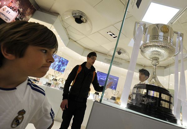A child looks at the replica of the King's Cup on display at the museum of the Santiago Bernabeu stadium in Madrid on April 22, 2011. Real Madrid has put a replacement for the King's Cup after the original was crushed during the celebrations that followed its win of the trophy for the first time since 1993. During a victory parade held through the streets of Madrid in the early hours of April 21, 2011, Real defender Sergio Ramos accidently dropped the trophy from the top of an open-top bus which then ran over it with its right wheel. AFP PHOTO / DOMINIQUE FAGET