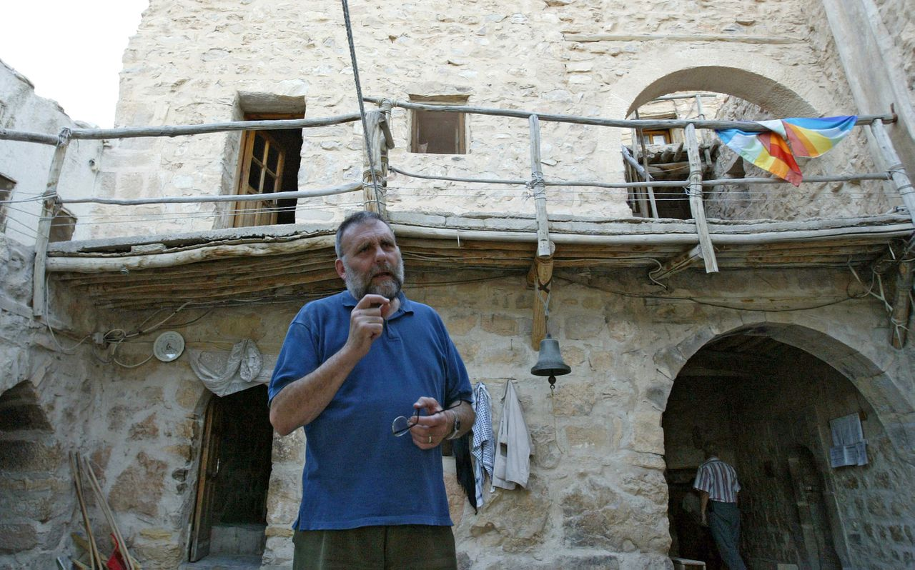 TO GO WITH AFP STORY ON MAR MOUSSA MONASTERY: Italian Father Paolo Dall'Oglio stands in a courtyard and talks to a visitor at the historic Monastery of Mar Moussa located near a summit on the the Qalamun massif, 80 km north of the Syrian capital Damascus, 11 July 2007. Over 900 years old, the Monastery of Mar Moussa, which houses some of the oldest frescos of the Christian East, would have fallen from memory into obscurity without the efforts and attention of an Italian priest impassioned from a dialogue with Islam. AFP PHOTO/LOUAI BESHARA