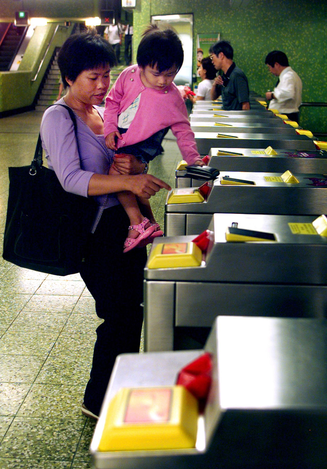 Een Hongkongse vrouw gebruikt in 2002 de chipkaart. Foto Reuters Passengers use Octopus card in Hong Kong metro station June 5, 2002. Most of the people carry an Octopus card - rechargeable, contactless card that is passed over a scanner to access almost every train, bus or ferry. The territory's 6.75 million inhabitants make nearly seven million Octopus transactions each day, worth about HK$48 million (US$6.12 million). REUTERS/Kin Cheung KC/BM