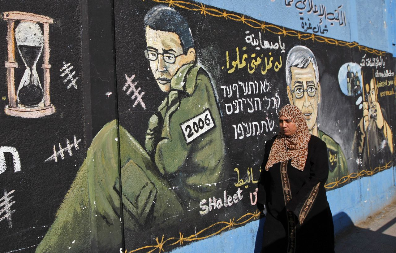 A Palestinian woman passes a mural depicting captured Israeli soldier Gilad Schalit as a young man and and a representation of him as an older man, as she walks in Jabaliya refugee camp, northern Gaza Strip, Wednesday, Dec. 23, 2009. The German mediator seeking to clinch a deal between Israel and Gaza's Hamas rulers to swap some 1,000 Palestinian prisoners for a single Israeli soldier arrived in Gaza on Wednesday, while Hamas studied Israel's most recent offer. (AP Photo/Khalil Hamra)