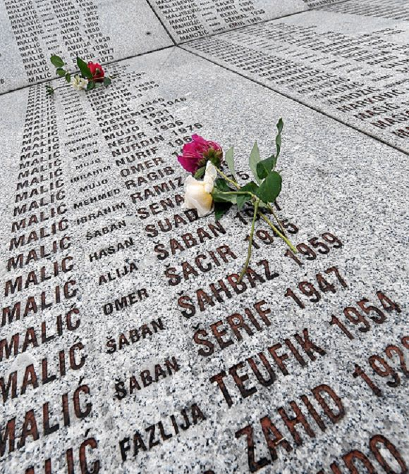 "Caption: Red and white roses have been left at the memorial wall with the names of victims the 1995 Srebrenica massacre at the Potocari memorial cemetery, near Srebrenica, on June 3, 2011. As the image of Ratko Mladic appeared on a television screen placed on a plateau in the vast Srebrenica cemetery, a stoney silence descended on the 20 women watching. Seated among the gravestones of the more than 4,500 victims of the Srebrenica massacre buried at the Potocari memorial centre, one of the women broke the silence, hissing: ""I hope God makes him burn in hell"". AFP PHOTO / ELVIS BARUKCIC"