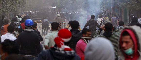 Caption: Protesters throw stones at riot police during clashes along a road which leads to the Interior Ministry, near Tahrir Square in Cairo November 21, 2011.Cairo police fought protesters demanding an end to army rule for a third day on Monday and morgue officials said the death toll had risen to 33, with many victims shot in the worst violence since the uprising that toppled President Hosni Mubarak. REUTERS/Amr Abdallah Dalsh (EGYPT - Tags: CIVIL UNREST POLITICS)