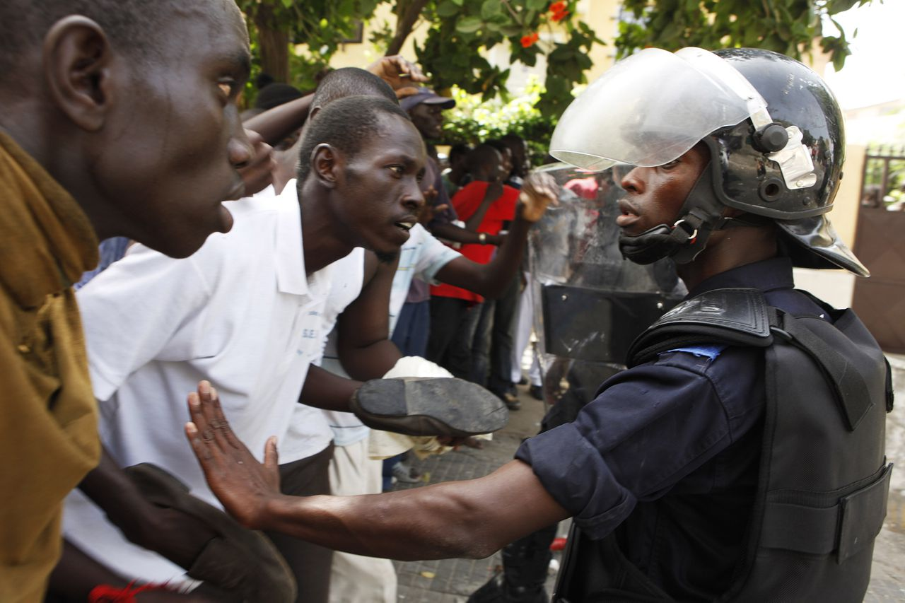 Protestors confront riot police outside the National Assembly during a demonstration in Senegal's capital Dakar June 23, 2011. Senegalese riot police fired rubber bullets, teargas and water cannon in running clashes with stone-throwing anti-government demonstrators in the heart of the capital Dakar on Thursday. Senegal President Abdoulaye Wade has withdrawn a proposed change to the country's electoral law, the government said, after the bill sparked clashes between riot police and protesters in the heart of the capital. REUTERS/Finbarr O'Reilly (SENEGAL - Tags: POLITICS CIVIL UNREST)