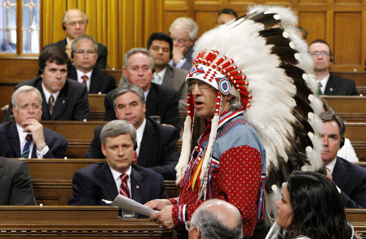 """Phil Fontaine, opperhoofd van de Assembly of First Nations, mocht gisteren een unieke toespraak houden in het Lagerhuis, waar normaal alleen leden het woord voeren. """"Dit is een nieuw begin."""" Foto Reuters Canada's Prime Minister Stephen Harper (bottom L) and other MP's listen as National Chief of the Assembly of First Nations Phil Fontaine (R) speaks in the House of Commons on Parliament Hill in Ottawa June 11, 2008. Canada, seeking to close one of the darkest chapters in its history, formally apologized on Wednesday for forcing 150,000 aboriginal children into grim residential schools, where many say they were abused. REUTERS/Chris Wattie (CANADA)"""