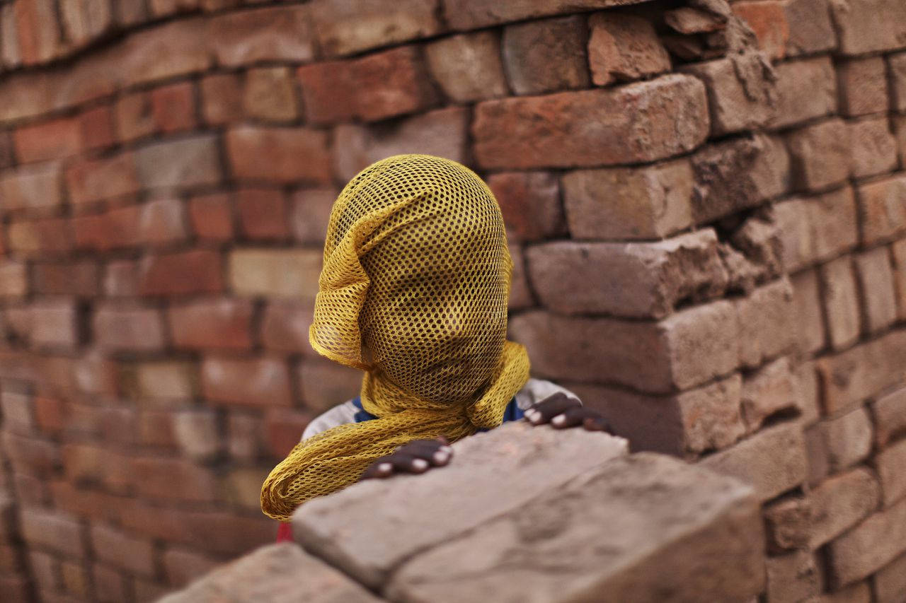 A Pakistani boy who lives near by a brick factory, covers his face with a scarf to avoid a sand storm, on the outskirts of Islamabad, Pakistan, Wednesday, June 6, 2012. (AP Photo/Muhammed Muheisen)
