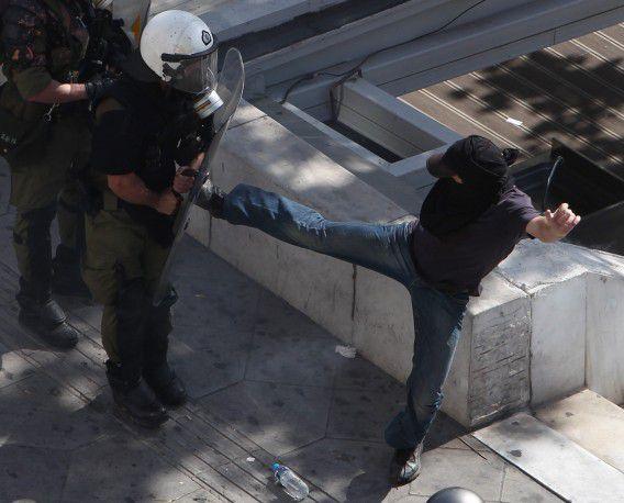 Een relschopper in gevecht met de oproerpolitie tijdens een 24-uursstaking in het centrum van Athene. Het is de tweede demonstratie die uitloopt op rellen in een maand. Foto AP /Thanassis Stavrakis