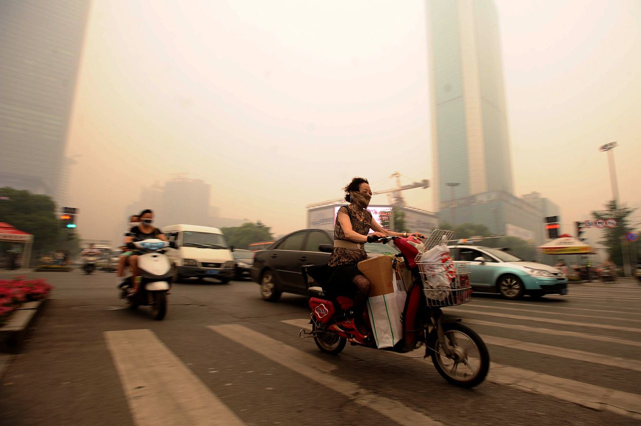 Chinese motorists wear masks as they make their way along a busy intersection in Wuhan, central China's Hubei province on June 11, 2012. The Chinese metropolis of Wuhan was blanketed by thick yellowish cloud, raising fears of pollution among its nine million inhabitants, as air pollution is increasingly acute in major Chinese cities and authorities are frequently accused of underestimating the severity of the problem in urban areas, especially in Beijing. CHINA OUT AFP PHOTO