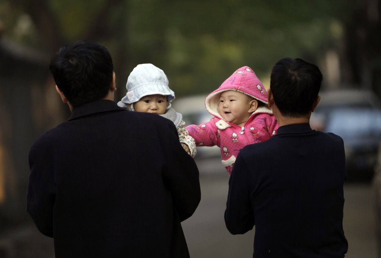 A 10-month-old girl touches a boy as her grandfather carries her as they walk along a traditional alleyway, or Hutong, in central Beijing November 6, 2012. REUTERS/Jason Lee (CHINA - Tags: SOCIETY SPORT SOCCER)