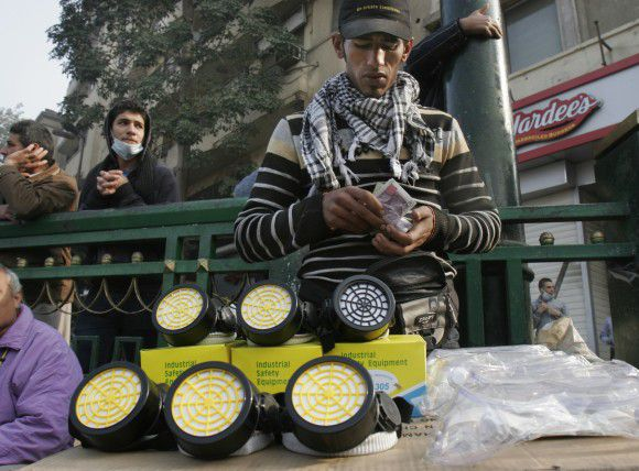 An Egyptian vendor sells gas masks in Tahrir Square in Cairo, Egypt, Thursday, Nov. 24, 2011. Police and protesters demanding that Egypt's ruling military council step down are observing a truce after five days of deadly street battles in which dozens have died. (AP Photo/Mohammed Abu Zaid)