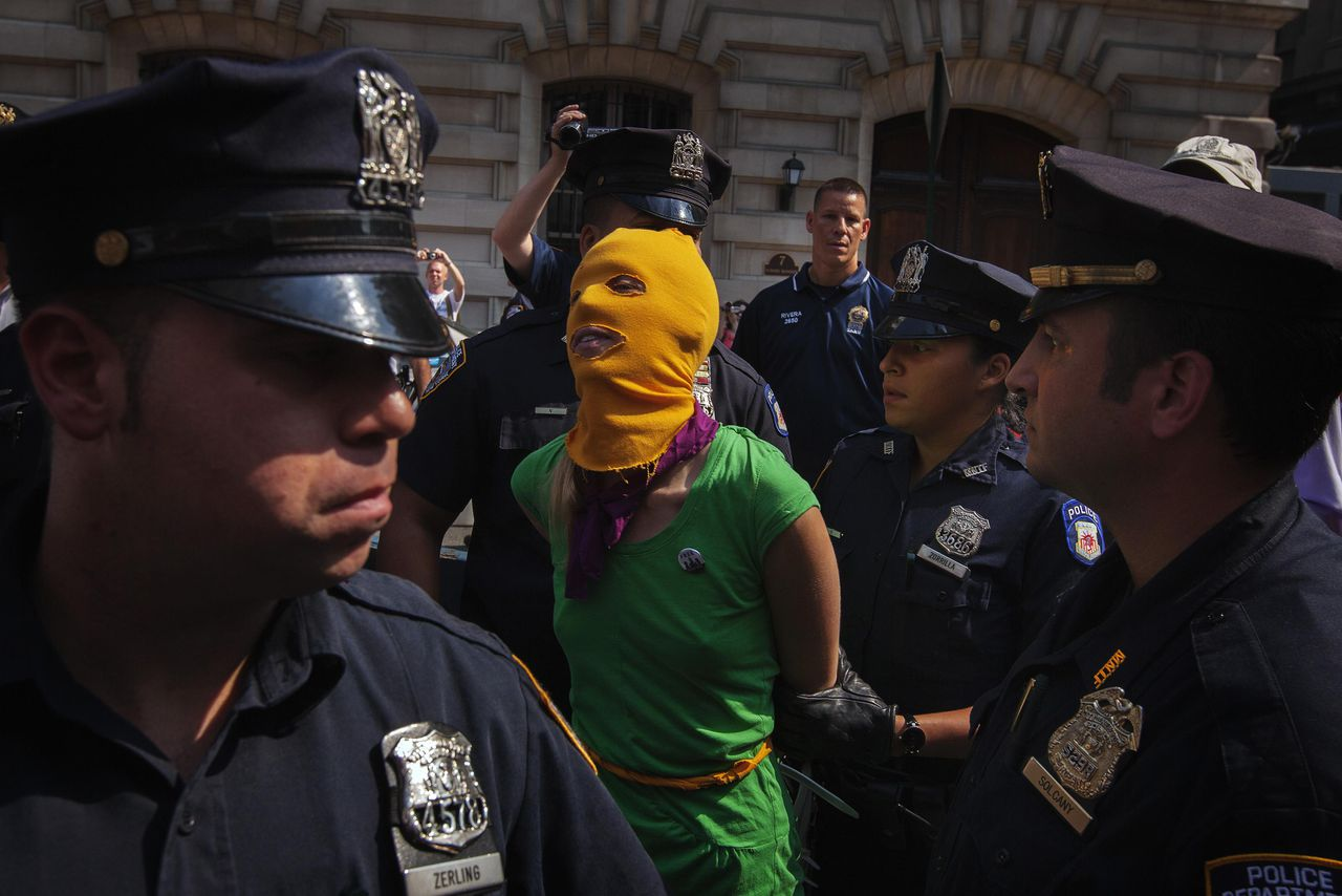 """New York Police Department officers arrest a woman demonstrating in solidarity with the Russian punk band Pussy Riot in front of the Russian Consulate in New York August 17, 2012. Three women from Russian punk band Pussy Riot were sentenced to two years in jail on Friday for their protest against President Vladimir Putin in a church, an outcome supporters described as the Kremlin leader's """"personal revenge"""". REUTERS/Lucas Jackson (UNITED STATES - Tags: CIVIL UNREST POLITICS TPX IMAGES OF THE DAY)"""