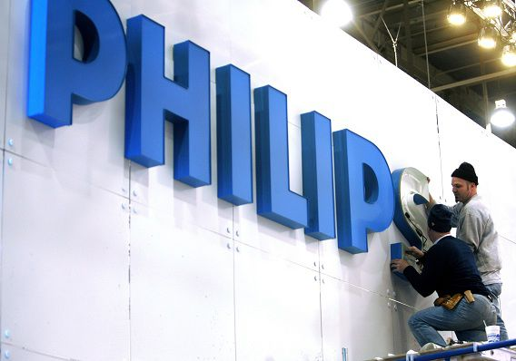 Workers put up a sign at the Philips Electronics booth before the Consumer Electronics Show (CES) at the Las Vegas Convention Center in this January 3, 2008 file photo. Philips is hiving off its once leading television business, the first step by new chief executive Frans van Houten to boost flagging profit at Europe's biggest consumer electronics maker. Philips is moving its loss-making TV business to a 30/70 joint venture with Hong-Kong based monitor maker TPV and has the option to sell out. The Dutch group has struggled to compete against players like Samsung and LG Electronics. Van Houten, a restructuring expert who took over as CEO this month, said on April 18, 2011 he is assessing the profitability of Philips' 400 or so business areas, a hint that further divestments could be on the cards. REUTERS/Las Vegas Sun/Steve Marcus/Files (UNITED STATES - Tags: SOCIETY BUSINESS)