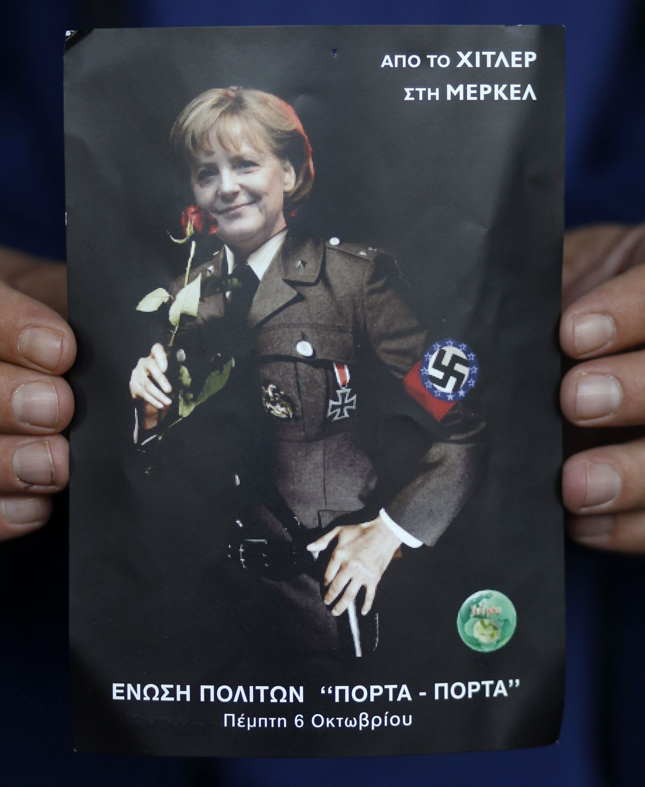 """A man displays a postcard-sized poster depicting German Chancellor Angela Merkel in a Nazi uniform with a swastika surrounded by the EU stars, in Athens October 28, 2011. Despite a deal clinched on Thursday at an EU summit to cancel half the value of Greece's 200 billion euro debt in the hands of private bondholders, many Greeks are deeply resentful of what they see as foreign meddling in their affairs, reviving memories of the wartime Nazi occupation. EU paymaster Germany, which has been vocal in demanding economic and fiscal reforms in return for its financial support, has become a target for demonstrators' derision. The accompanying words read """"From Hitler to Merkel"""" and """"Citizens Movement Porta-Porta"""". REUTERS/Yannis Behrakis (GREECE - Tags: CIVIL UNREST POLITICS BUSINESS)"""
