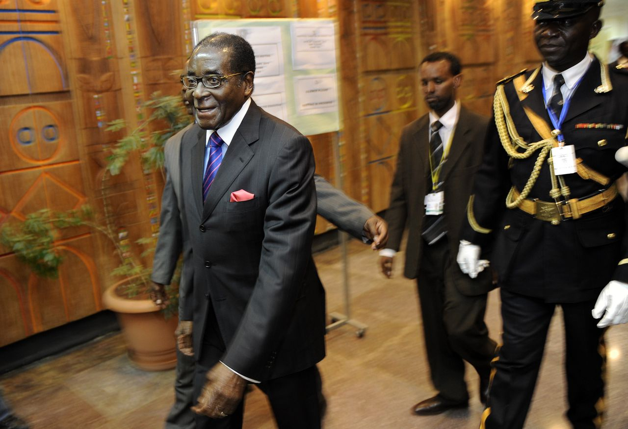 """Zimbabwe President, Robert Mugabe (L) arrives January 28, 2011 at the 16th ordinary session of the African Union, AU, in the Ethiopian capital, Addis Ababa. Kenya's Prime Minister, Raila Odinga, the African Union mediator in the Ivory Coast political crisis on Friday called for direct talks between presidential rivals Laurent Gbagbo and Alassane Ouattara. The Kenyan Prime Minister Raila Odinga said an AU summit starting on Sunday should """"send a strong and unequivocal message that the two parties must negotiate face-to-face."""" AFP PHOTO/Tony KARUMBA"""