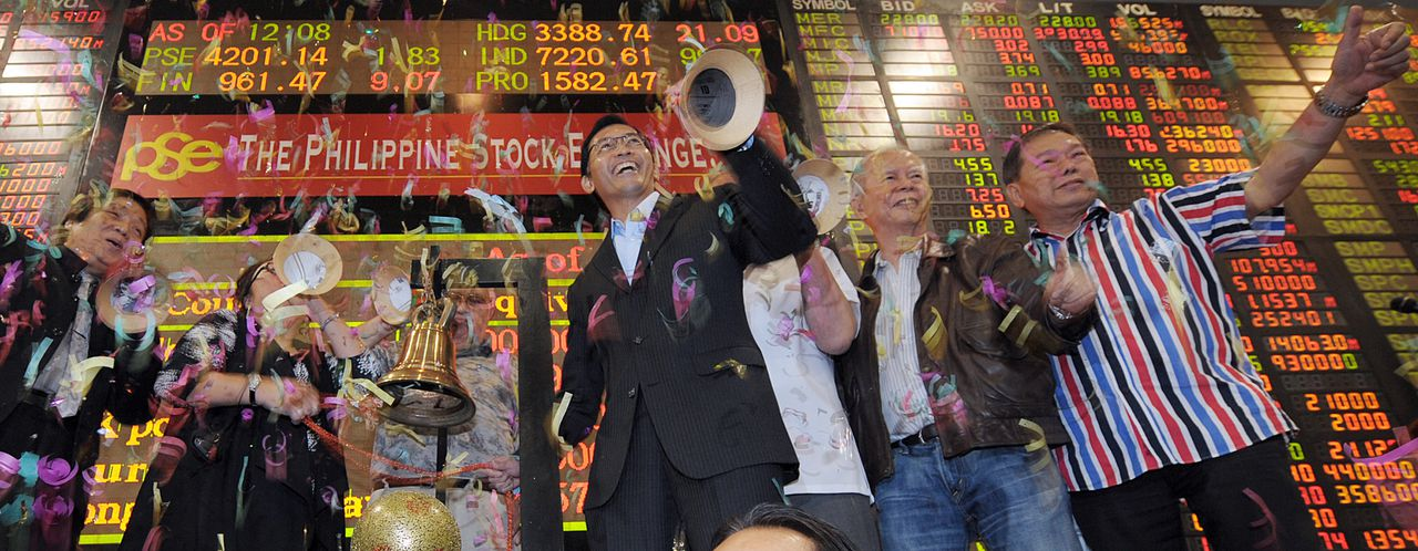Philippine Stock Exchange traders celebrate on the last day of trading in front of a giant electronic board at the Philippine Stock Exchange in Manila on December 30, 2010. Asian stock markets were mixed, with some signs of optimism going into 2011 but Beijing's efforts to cool the Chinese economy dampening spirits. AFP PHOTO