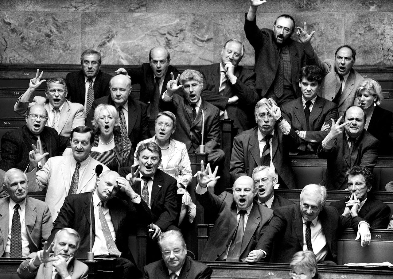 """Franse oppositieleden in de Assemblée Nationale reageren op een toespraak van Nicolas Sarkozy twee jaar geleden, toen hij nog minister van Binnenlandse Zaken was Foto AFP French opposition deputies react to the speech of French Interior minister Nicolas Sarkozy (not pictured) 22 June 2005 during a session of questions to the government at the National Assembly in Paris. Sarkozy talked earlier of """"cleaning up blockhouses"""" in suburbs following the killing of a 11-year-old child in La Courneuve, north of Paris on Sunday. AFP PHOTO JOEL ROBINE"""