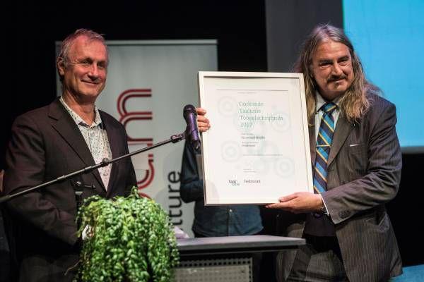 Schrijver Ilja Leonard Pfeijffer neemt de Taalunie Toneelschrijfprijs 2017 in ontvangst uit handen van Hans Bennis.