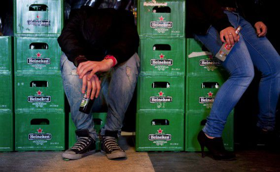 Een jongen zit laveloos tussen de kratten bier.