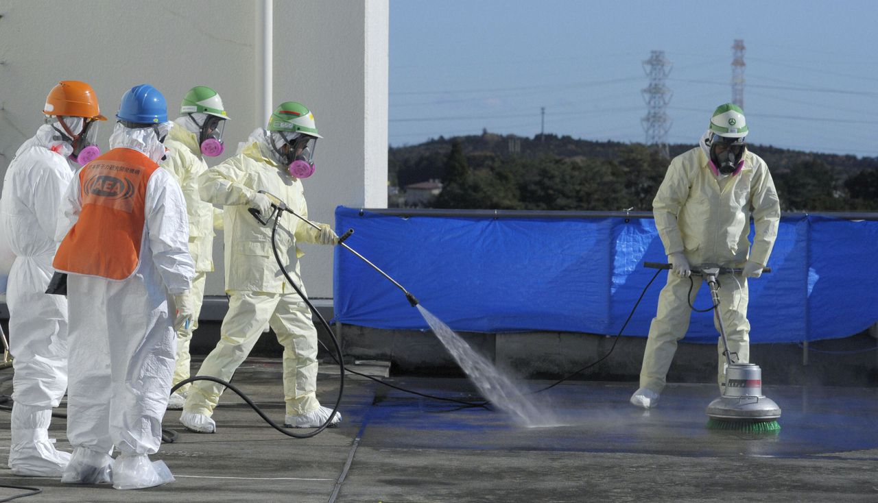 Workers decontaminate the roof of the Okuma town office near the tsunami-crippled Fukushima Daiichi nuclear power plant in Fukushima prefecture, in this photo taken by Kyodo on December 4, 2011. The tsunami that struck Fukushima nuclear plant in March was far larger than what the facility was equipped to handle, the operator of the plant said on Friday in its first official assessment of the worst nuclear disaster in 25 years. REUTERS/Kyodo (JAPAN - Tags: DISASTER BUSINESS ENVIRONMENT) MANDATORY CREDIT. JAPAN OUT. NO COMMERCIAL OR EDITORIAL SALES IN JAPAN. FOR EDITORIAL USE ONLY. NOT FOR SALE FOR MARKETING OR ADVERTISING CAMPAIGNS. THIS IMAGE HAS BEEN SUPPLIED BY A THIRD PARTY. IT IS DISTRIBUTED, EXACTLY AS RECEIVED BY REUTERS, AS A SERVICE TO CLIENTS. YES