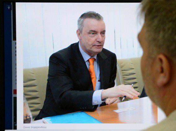 Een man kijkt op zijn computer naar een afbeelding van de mishandelde Nederlandse diplomaat Onno Elderenbosch