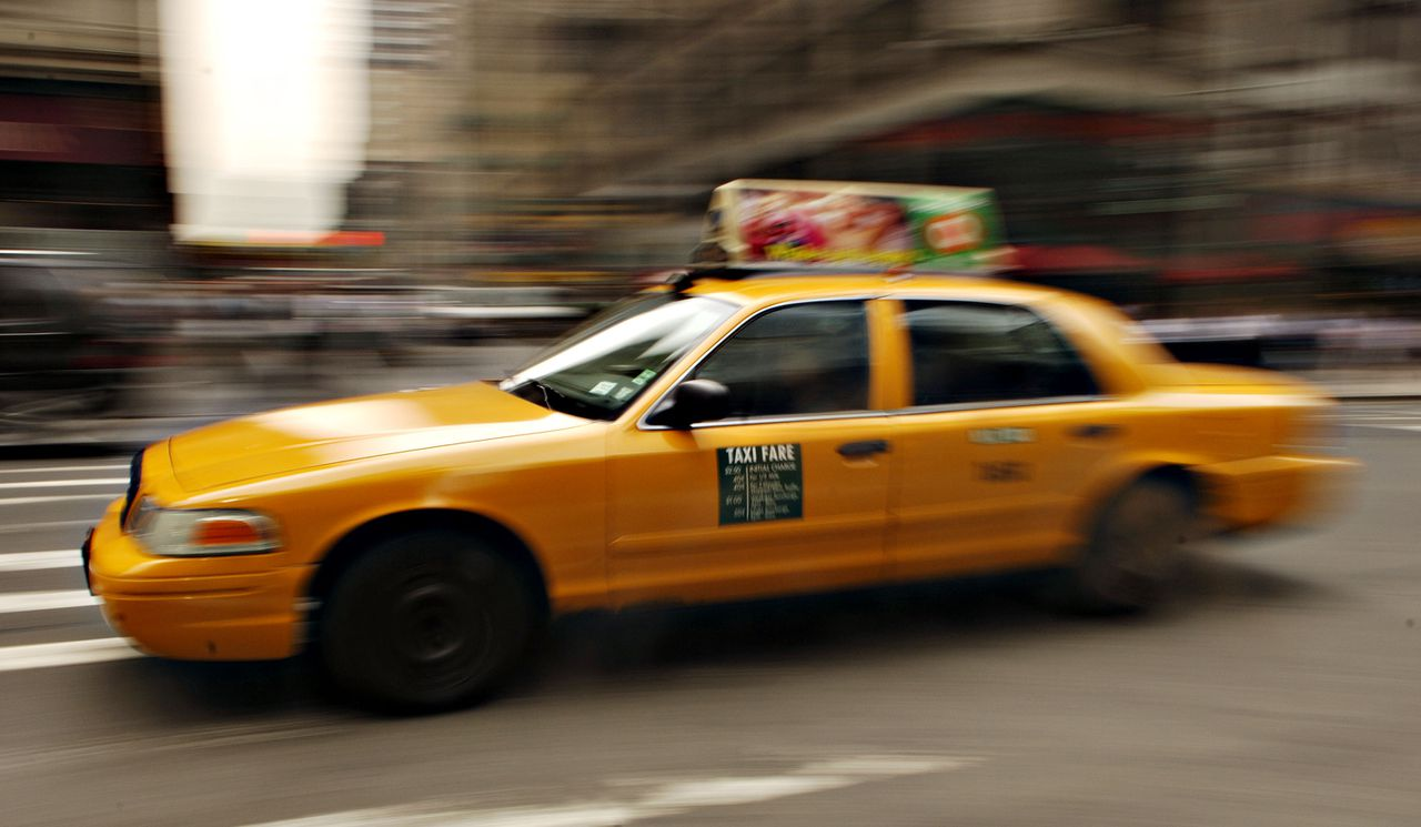 A taxi drives down 5th Avenue in New York, Wednesday, June 14, 2006. In New York, the capital of world finance, the hottest investment isn't stocks, bonds, commodities or even Manhattan apartments. It's taxi medallions, the metal plates affixed to the hoods of the city's 12,779 yellow cabs. Photographer: Daniel Acker/Bloomberg News.