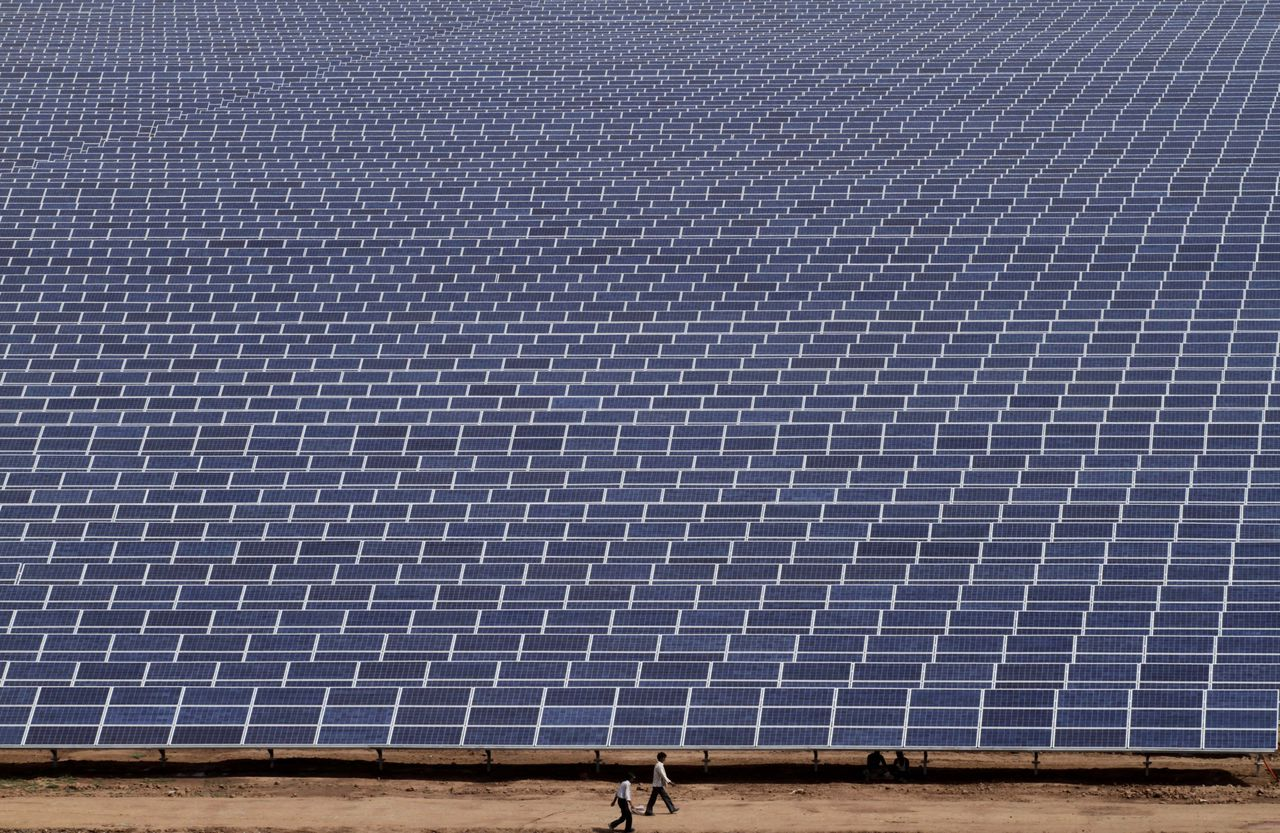 Indian workers walk past solar panels at the Gujarat Solar Park at Charanka in Patan district, about 250 kilometers (155 miles) from Ahmadabad, India, Saturday, April 14, 2012. Gujarat state Chief Minister Narendra Modi will dedicate the 200 megawatt solar power park, along with other solar projects totaling 600 megawatts of power on April 19. (AP Photo/Ajit Solanki)