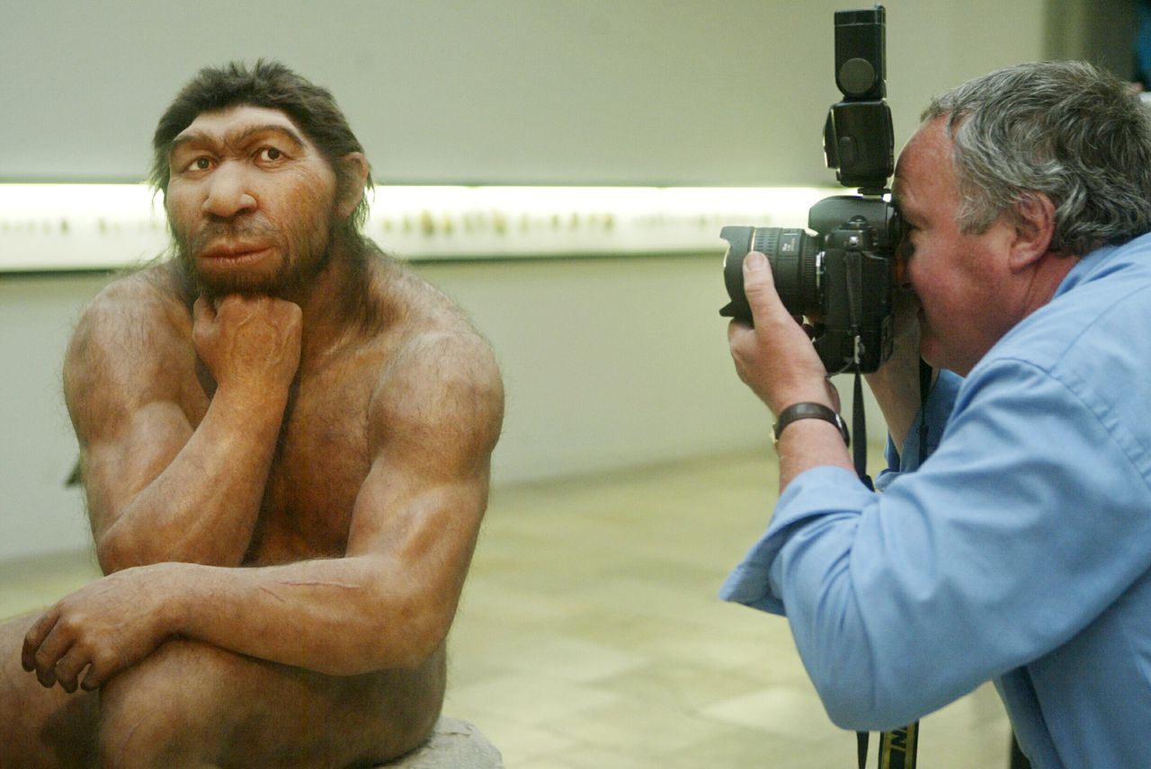 TO GO WITH AFP STORY (FILES) File picture taken 28 July 2004 shows a photographer taking pictures of the Neanderthal man ancestor's reconstruction, displayed in a show of the Prehistoric Museum in Halle, eastern Germany. Germany celebrates 2006 the 150 anniversary of the Neanderthal man's first discovery by quarry workers in the Neander valley, near Dusseldorf in August 1856. AFP PHOTO DDP/MICHAEL LATZ GERMANY OUT