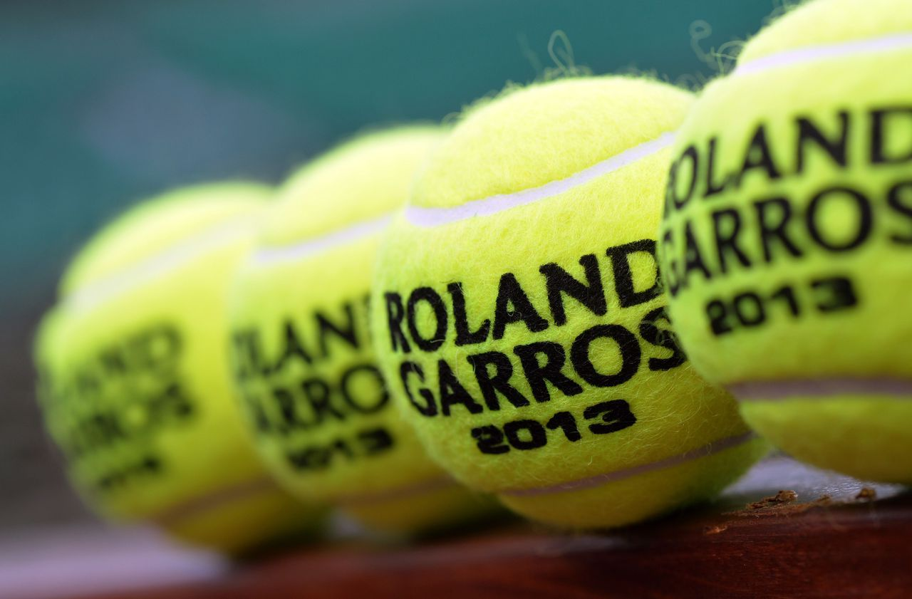 Official tennis balls of the 2013 French Open are pictured on a court at the Roland Garros stadium in Paris on May 22, 2013, ahead of the start of the tournament. AFP PHOTO / MIGUEL MEDINA