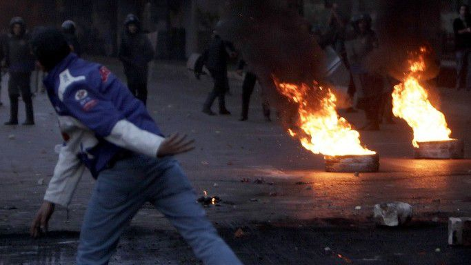 Anti-government protesters clash with riot police near burning tyres placed as a barricade during clashes in Cairo January 26, 2011. Thousands of Egyptians defied a ban on protests by returning to Egypt's streets on Wednesday and calling for President Hosni Mubarak to leave office, and some scuffled with police. REUTERS/Amr Abdallah Dalsh (EGYPT - Tags: CIVIL UNREST POLITICS)