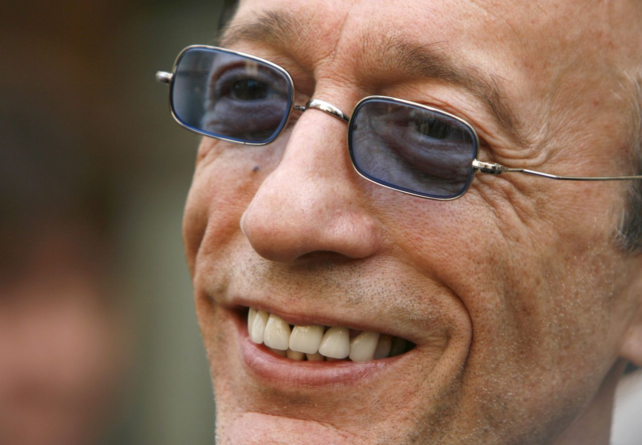 Robin Gibb of the Bee Gees watches the unveiling of a green plaque on the front of a building, in central London in this May 10, 2008 file photo. Bee Gees singer Gibb, who with brothers Barry and Maurice helped define the disco era with their falsetto harmonies and funky beats, died on May 20, 2012. He was 62. REUTERS/Luke MacGregor/Files (BRITAIN - Tags: ENTERTAINMENT PROFILE HEADSHOT)