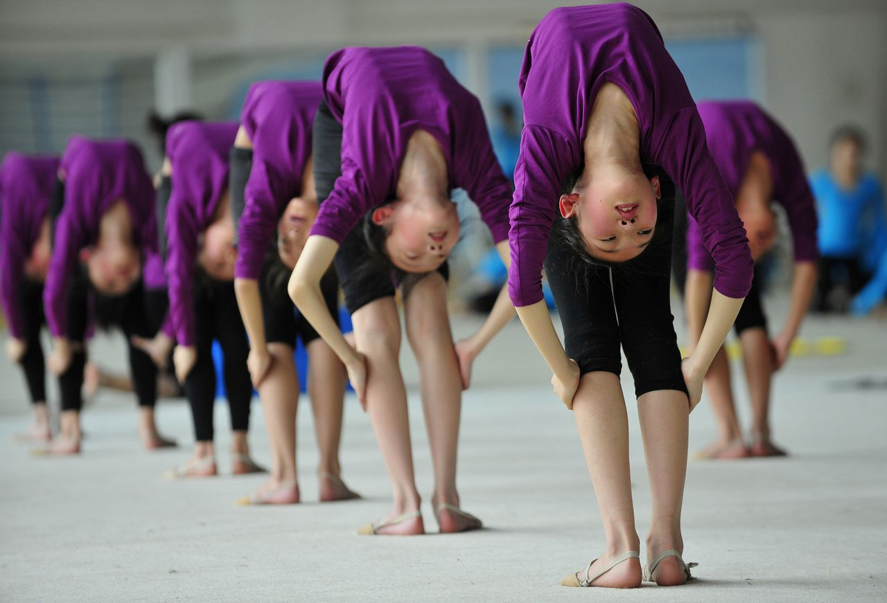 Students stretch during a training session at a gymnastic course at Shenyang Sports School in Shenyang, Liaoning province May 9, 2012. Some 60 students, between the ages of 6 to 15, undergo a nine-year gymnastic programme which includes foundation courses and gymnastic training courses at Shenyang Sports School, and those who are outstanding may be selected to join the national team, according to local media. Picture taken May 9, 2012. REUTERS/Stringer (CHINA - Tags: EDUCATION SPORT GYMNASTICS)