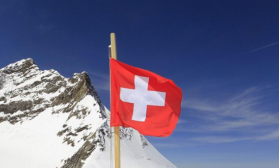 Tourists take pictures beside a Swiss national flag at the Jungfraujoch (3,572 metres/11,782 ft) in front of the peak Mount Jungfrau (4,158 metres/13,642 ft) during sunny spring weather near the Swiss mountain resort of Grindelwald in the Bernese Alps May 24, 2012. REUTERS/Arnd Wiegmann (SWITZERLAND - Tags: TRAVEL ENVIRONMENT)