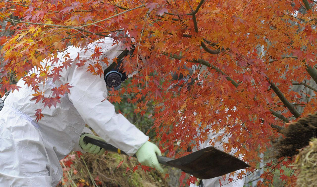 A member of Japan's Ground Self-Defense Force wearing a protective suit removes contaminated soil from areas tainted with radioactive substances from the Fukushima Daiichi Nuclear Power plant, near the Tomioka town hall in Tomioka town, Fukushima Prefecture, in this picture distributed by Kyodo December 8, 2011. The Japanese government may inject about $13 billion into Tokyo Electric Power Co as early as next summer in a de facto nationalisation of the operator of the crippled Fukushima nuclear power plant, sources said on Thursday. Mandatory Credit REUTERS/Kyodo (JAPAN - Tags: DISASTER ENERGY ENVIRONMENT BUSINESS) FOR EDITORIAL USE ONLY. NOT FOR SALE FOR MARKETING OR ADVERTISING CAMPAIGNS. THIS IMAGE HAS BEEN SUPPLIED BY A THIRD PARTY. IT IS DISTRIBUTED, EXACTLY AS RECEIVED BY REUTERS, AS A SERVICE TO CLIENTS. MANDATORY CREDIT. JAPAN OUT. NO COMMERCIAL OR EDITORIAL SALES IN JAPAN. YES