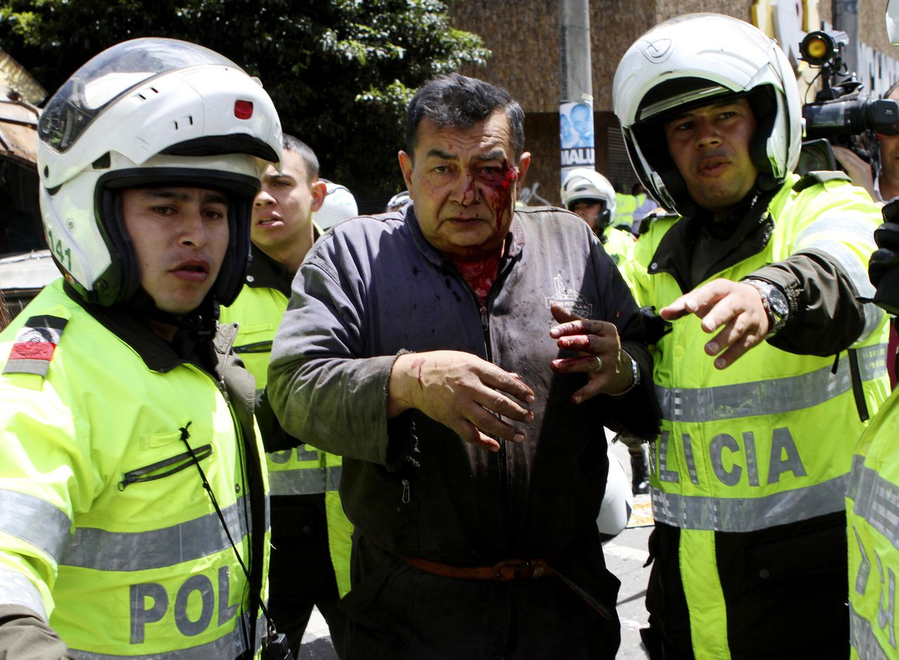 An injured man is aided by policemen at the scene of an explosion in a central avenue in Bogota May 15, 2012. A bomb attack in a commercial district of Colombia's capital Bogota killed two people on Tuesday and injured a former interior minister who was the target, President Juan Manuel Santos said. REUTERS/Fredy Builes (COLOMBIA - Tags: POLITICS CIVIL UNREST CRIME LAW)