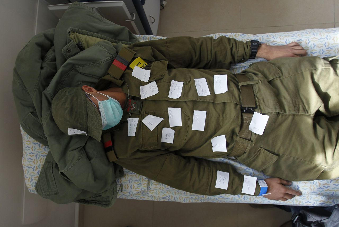 An Israeli soldier, with notes stuck on him describing his symptoms, plays the role of a mock victim during a drill simulating an unconventional weapons' attack, at Haemek hospital in the northern Israeli city of Afula November 30, 2011. REUTERS/Baz Ratner (ISRAEL - Tags: HEALTH CIVIL UNREST MILITARY)