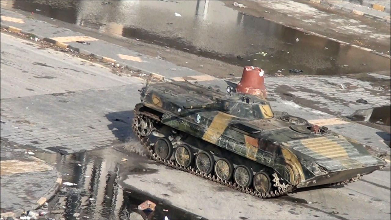 "Video grab shows a Syrian tank driving through the city of Homs on December 26, 2011. Heavy gunfire killed 23 people in Syria's besieged city of Homs today as newly arriving Arab League observers were urged to head immediately to one of the country's most serious hot spots. Yesterday, the opposition Syrian National Council (SNC) said Homs was under siege and facing an ""invasion"" from some 4,000 troops deployed near the city that has become a focal point of the uprising against President Bashar al-Assad. AFP PHOTO"