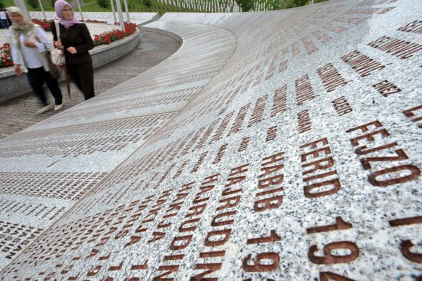 "Bosnian Muslim women walk past the memorial wall with the names of victims the 1995 Srebrenica massacre at the Potocari memorial cemetery, near Srebrenica, on June 3, 2011. As the image of Ratko Mladic appeared on a television screen placed on a plateau in the vast Srebrenica cemetery, a stoney silence descended on the 20 women watching. Seated among the gravestones of the more than 4,500 victims of the Srebrenica massacre buried at the Potocari memorial centre, one of the women broke the silence, hissing: ""I hope God makes him burn in hell"". AFP PHOTO / ELVIS BARUKCIC"